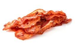 Close-up cozinhado das fatias de toucinho do bacon em um fundo branco imagem de stock royalty free