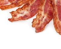 Close-up cozinhado das fatias de toucinho do bacon isolado como um fundo fotografia de stock royalty free
