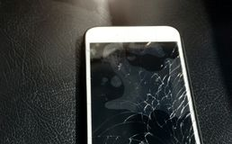 Close up of cracked smartphone screen lay on black leather.  royalty free stock images