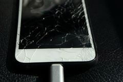 Close up of cracked smartphone screen lay on black leather.  stock photography