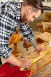Close-up of craftsman sanding a guitar neck in wood at workshop. Close-up of carpenter using sanding paper on a guitar neck in a workshop for wood. Hard working royalty free stock image