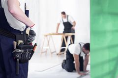 Close-up of craftsman with toolbelt during home renovation work. Blurred background stock photos