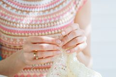 Close up of craftswoman`s hands knitting dress with crochet. Female working with tender lace. Business handmade crochet relaxatio royalty free stock images