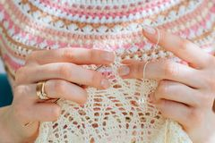 Close up of craftswoman`s hands knitting dress with crochet. Female working with tender lace. Business handmade crochet relaxatio stock photo