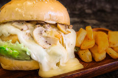 Close-up of Cream mushroom sauce Burger with French fries on wood plate with copy space. Close-up of Cream mushroom sauce Burger with French fries Stock Photos