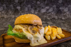 Close-up of Cream mushroom sauce Burger with French fries on wood plate with copy space. Close-up of Cream mushroom sauce Burger with French fries Stock Images