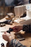 Close-up creates the shape of a butterfly tie made of wool. Good looking young man working as a tailor and using a. Good looking young man working as a tailor Royalty Free Stock Images