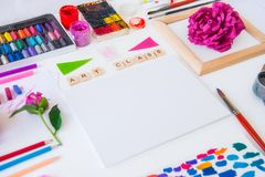 Close up creative artist workplace. Blank Canvas, Art class lettering on wooden blocks and colorful painting materials on white. Background. Art therapy stock photography