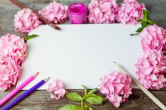 Close up creative layout made of pink wisteria flowers, canvas blank, brushes, fuchsia color gouache paint, color pencils on the o. Ld wooden rustic table. Art royalty free stock photo