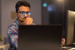 Close up of creative man working at night office. Deadline, technology and people concept - close up of creative man in glasses working at night office and Stock Images