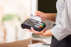 Close up of credit card machine, a woman hand swaping a gray card Royalty Free Stock Photos