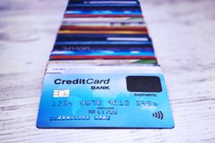 Close up of credit cards stack on wooden surface. Bunch of payment cards with biometric card lying on the top. Concept of paying. For purchases using stock photos