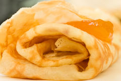 Close up of a crepe with marmalade filling. Close up of a homemade crepe with orange colored jam filling, shallow depth of field royalty free stock image