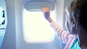 Close-up a criança que a menina abaixa a cortina da vigia na cabine do avião, de lá brilha uma luz brilhante Menina lindo filme