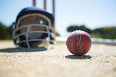 Close up of cricket ball with helmet on pitch Stock Photo