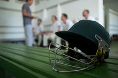 Close up of cricket helmet on table against team. In locker room royalty free stock photos