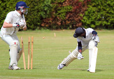 Close up of cricket player bowled out. A close up of a cricket batsman and the bails of his stump flying through the air Royalty Free Stock Photo