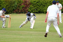 Close up of cricket player bowled out. A close up of a cricket batsman and the bails of his stump flying through the air Stock Photography