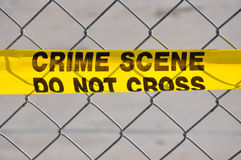 Close up of Crime Scene Do Not Cross. Closeup of Bright yellow Crime Scene Do Not Cross tape against a chain link fence Royalty Free Stock Photo