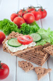 Close up of crispbreads with soft cheese and vegetables Royalty Free Stock Photos