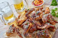 Chicken wings glass cups of beer royalty free stock photography