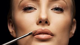 Close up crop of female face applying make up. Close up female face with makeup lipstick brush. Young woman applying lip gloss with make up brush on lips. Tight Royalty Free Stock Image
