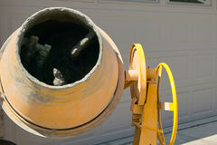 Yellow industrial cement mixer concreting machine. Close up crop of a yellow cement mixer concreting machine in a home drive way Royalty Free Stock Images