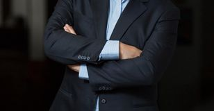 Close up cropped caucasian man hands and arms folded in a smart. Navy suit Royalty Free Stock Photos