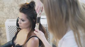 A close-up, cropped frame, a beautiful young brunette with a deep neckline sits in a hairdresser`s chair, does her stock video footage