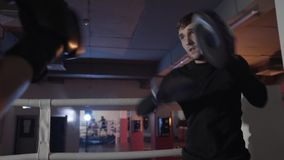 A close-up of a cropped frame of a boxing trainer is training his pupil. The training of fighting equipment, boxing stock footage
