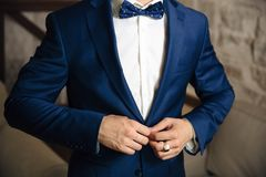 Close-up of a cropped frame of a man buttoning his stylish jacket over a button, wearing a white shirt and a bow tie, a. Businessman wearing a gold ring on his Royalty Free Stock Photos