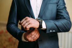 A close-up of a cropped frame of a man in an expensive classic costume looks at his watch. The businessman is in a hurry royalty free stock photography