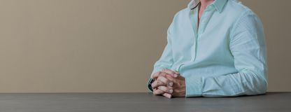 Close up cropped hands and arms of businessman in a light blue c. Olor shirt sitting at a desk with an olive brown wall behind Stock Photos