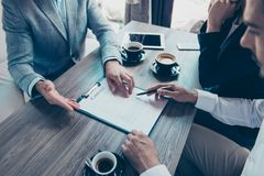 Close up cropped high angle view of young people making a deal w. Ith lawyer about their business in cafe with cups of coffee. Men is going to sign contract to Royalty Free Stock Photo