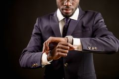 Close up cropped image african male of setting of watch. Live according to timetable. synchronize watches Royalty Free Stock Image