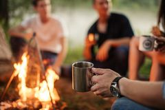 Close up cropped photo. focus on the man`s hand holding metal cup. Hikers on the blurred background of the photo royalty free stock photography