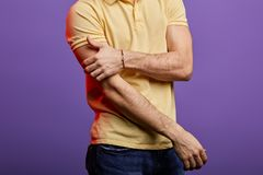 Close up cropped photo. man in yellow T-shirt and jeans stretching his arm, cricking. Close up cropped photo royalty free stock photos