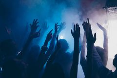 Close up cropped photo of people raised hands up in blue whire s stock photos