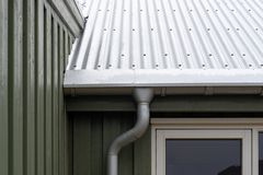 Close up cropped photo of small green house with zinc metallic rain gutter on cornice under rivets roof.  royalty free stock photos