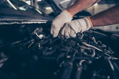 Close up cropped shot of experts appraisal of damage for repairi. Ng car at auto workshop, arms in white knitted gloves. Mounting specialist working at vehicle Royalty Free Stock Image