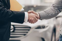 Car salesman working with a customer at the dealership. Close up cropped shot of a men shaking hands with professional car dealer at automobile dealership stock photos