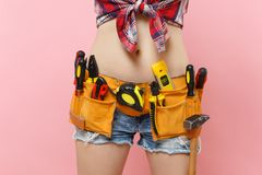 Close up cropped shot tummy of strong young handyman woman with kit tools belt full of variety useful instruments royalty free stock photo