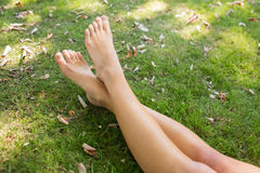 Close up of crossed legs of a woman lying on the grass Royalty Free Stock Images