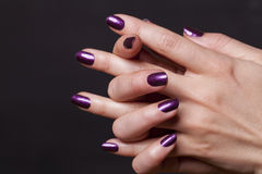 Close up of crossed over female hands. Decorated with purple fingernail paint over black stock photos