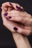 Close up of crossed over female hands. Decorated with purple fingernail paint over black royalty free stock photos