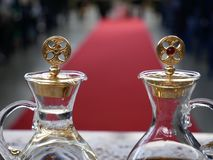 Close up of cruets with water and wine ready for catholic mass with red carpet and people in the background stock photo