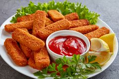 Close-up of crumbed fish sticks, top view. Close-up of crumbed fish sticks served on a white plate with lemon, lettuce leaves and tomato sauce, vertical view royalty free stock photos