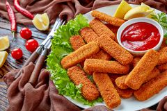 Close-up of crumbed fish sticks, top view. Crumbed fish sticks served on a white plate with lemon, lettuce leaves and tomato sauce, horizontal view from above stock photo