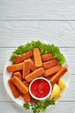 Close-up of crumbed fish sticks, top view. Overhead view of crumbed fish sticks served with lemon, lettuce leaves and tomato sauce on a white plate on a wooen royalty free stock images