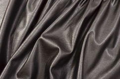 Close up on crumpled black leather material textured fabric. Royalty Free Stock Images